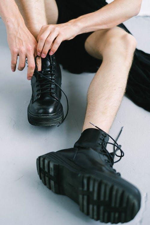 Crop faceless trendy guy tying shoelaces of boots on floor