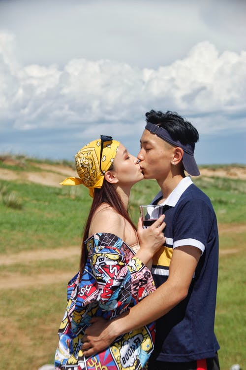 Side view young stylish Asian couple embracing and kissing gently while spending sunny summer day in nature together