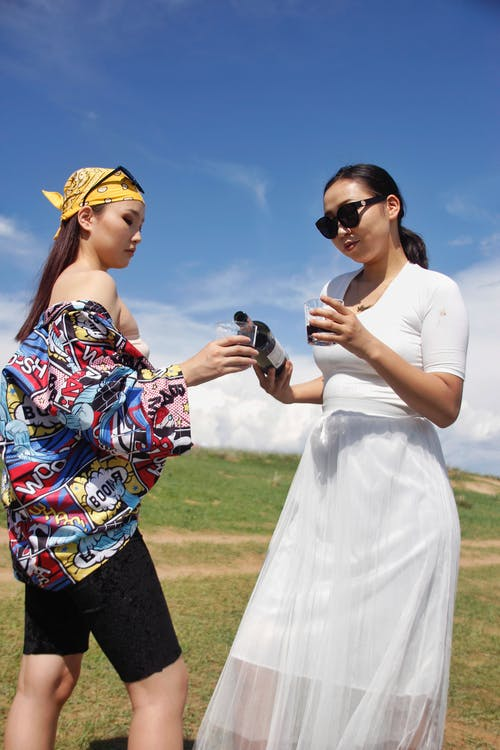 Young attractive Asian females in trendy summer outfits pouring red wine into glasses while standing on lush grassy valley in countryside