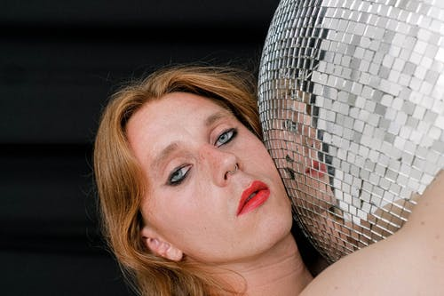 Alluring young person with red lips hugging disco ball
