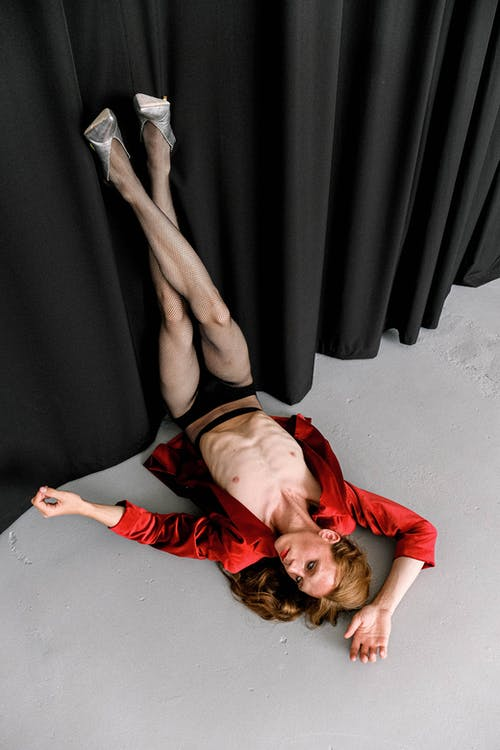 From above of extravagant skinny young transsexual male dancer in provocative clothes and high heeled shoes lying on floor with raised legs near black curtain