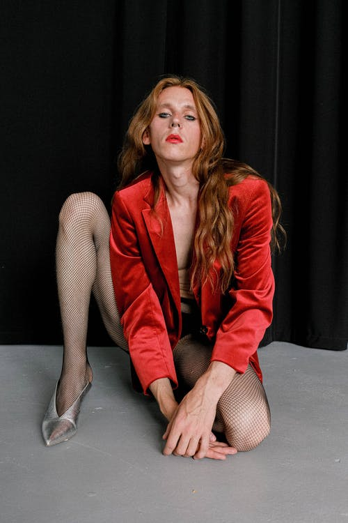 Full length of confident young transsexual male dancer with long wavy hair in eccentric outfit and high heeled shoes sitting on knee and looking at camera