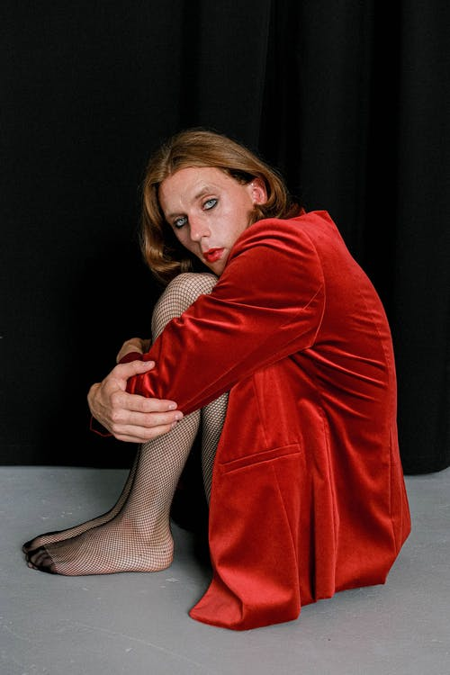 Melancholic young androgynous guy embracing knees and looking at camera