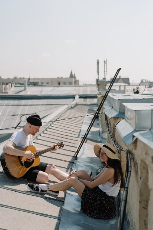 2 Women Sitting on White and Brown Boat Playing Guitar