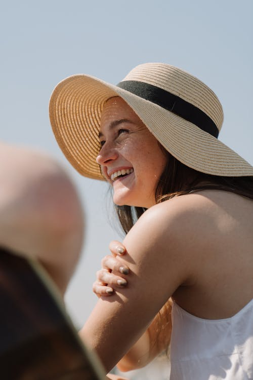 Woman in Black Tank Top Wearing Brown and White Fedora Hat