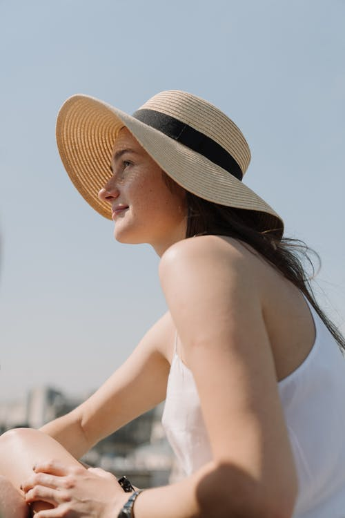 Woman in White Off Shoulder Dress Wearing Brown Straw Hat