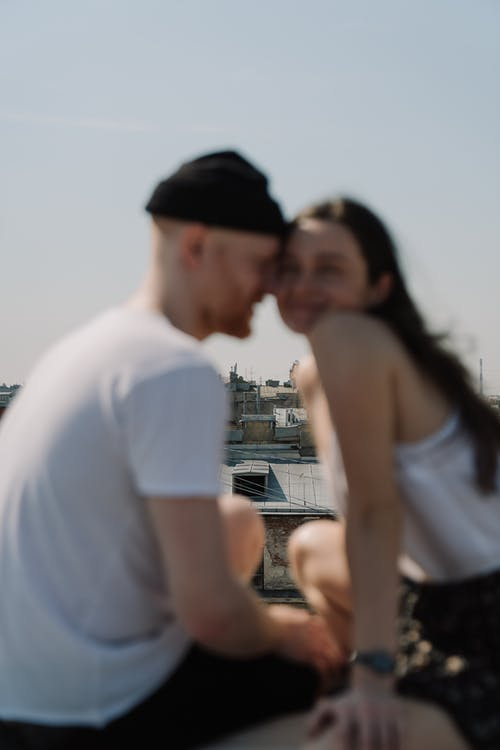 Man in White T-shirt Kissing Woman in Black Tube Dress