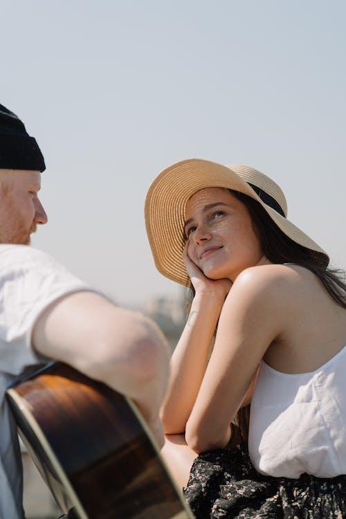 Man in White Shirt Hugging Woman in Black Hat