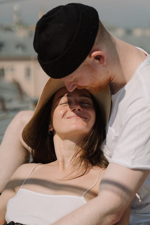 Man in White Shirt Kissing Woman in Brown Hat