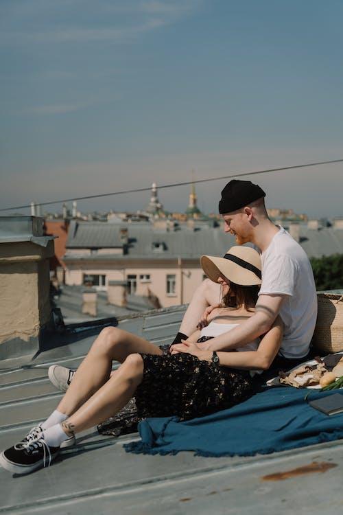 Frau Im Schwarzen Und Weißen Blumenkleid, Das Weißen Hut Sitzt, Der Auf Blauem Textil Sitzt