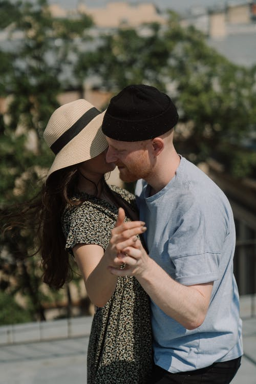 Man in Blue Button Up Shirt Kissing Woman in Black and White Shirt