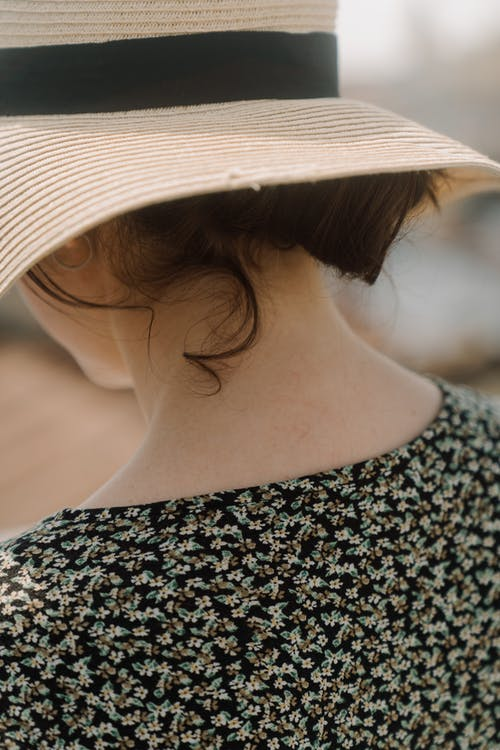 Woman in Black and White Shirt Wearing White Sun Hat
