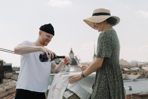 Man in White T-shirt Holding Woman in Black and White Dress