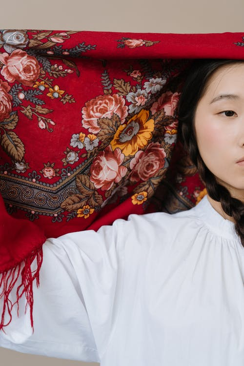 Girl in White Crew Neck Shirt Lying on Red and Brown Floral Textile