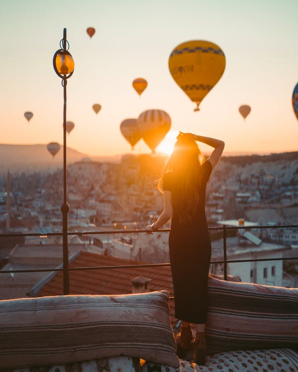 Woman Holding Yellow Balloons during Sunset