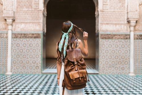 A Woman Carrying a Brown Leather Rucksack