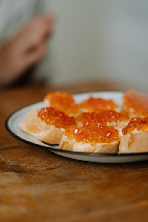 Sliced of Bread With Orange and White Cream on White Ceramic Plate