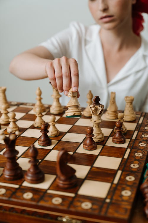 Person Playing Chess Game on Chess Board