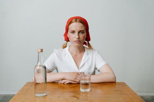 Woman in White Dress Shirt Wearing Red Bandana Sitting Beside Brown Wooden Table