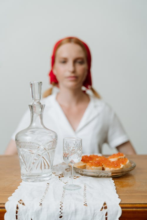 Woman in White Dress Shirt Sitting Beside Table With Food