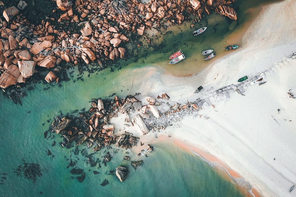 Boats floating in water near rocky shore