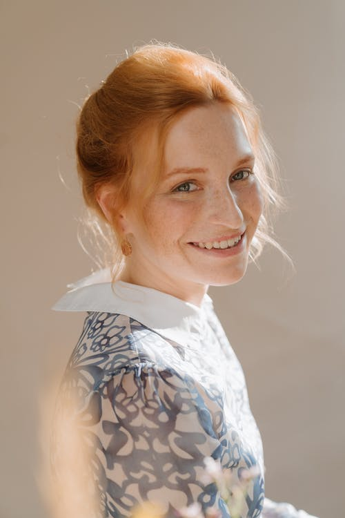 Woman in White and Blue Floral Shirt Smiling