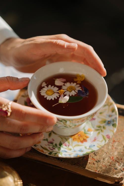 Person Holding White Ceramic Teacup With Tea