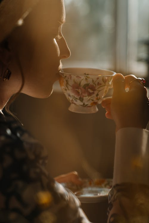 Woman Holding White and Red Floral Ceramic Teacup