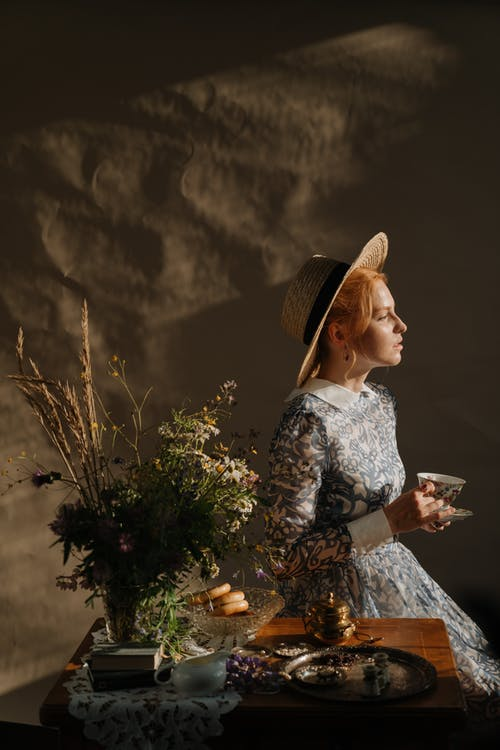 Woman in White and Black Floral Dress Wearing Brown Sun Hat Standing Beside Green Plants during