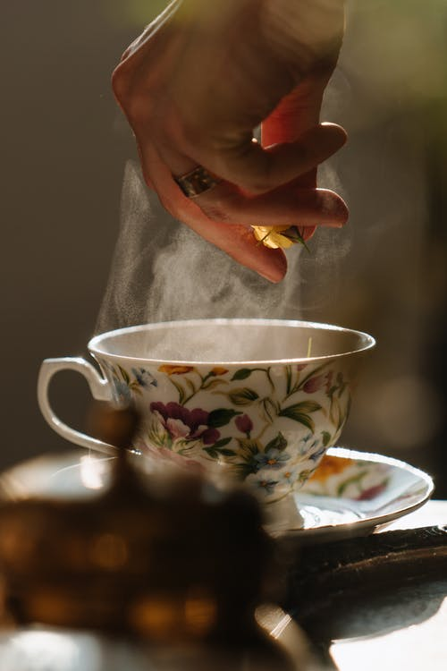 Person Holding White and Red Floral Ceramic Teacup