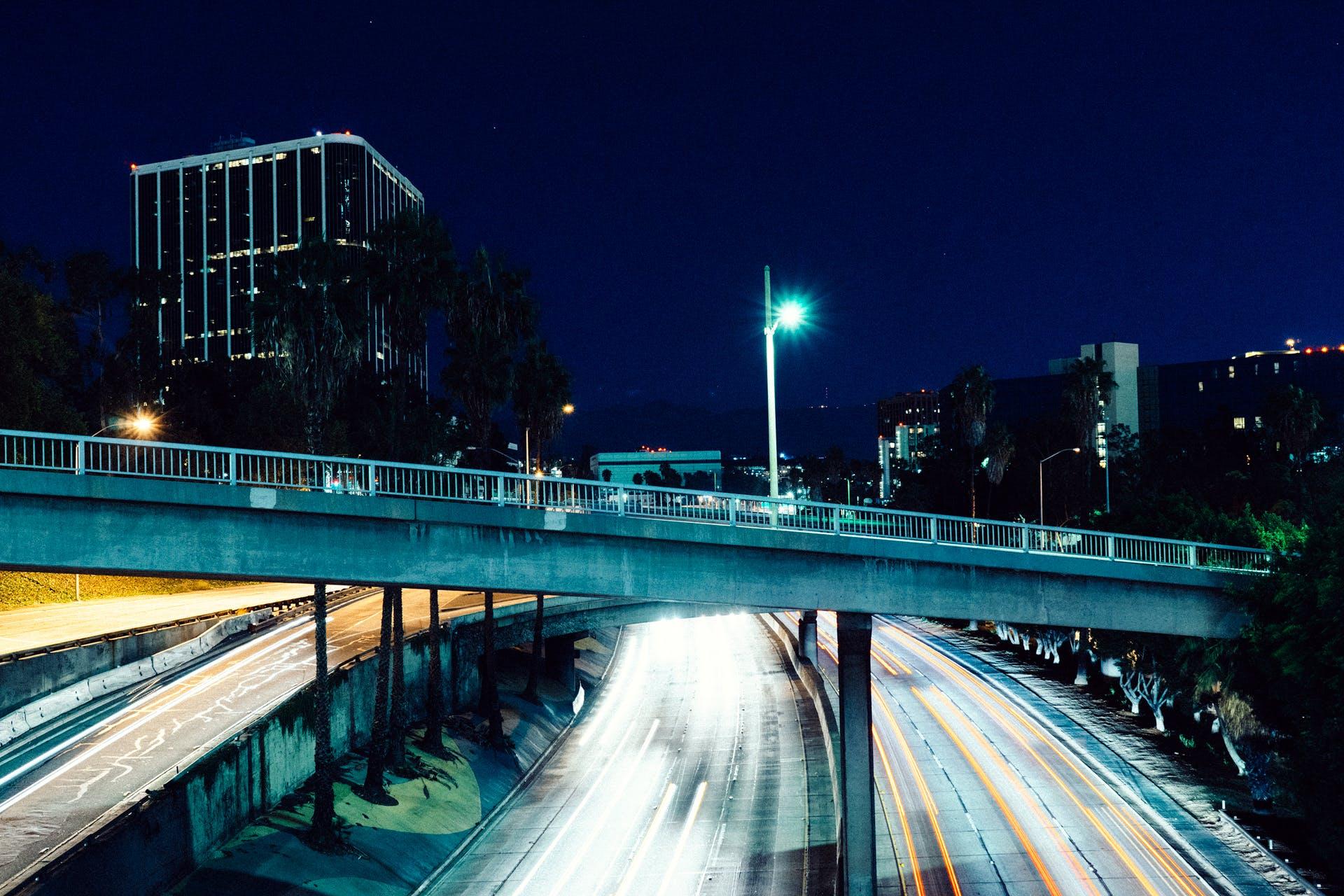 Gray Concrete Bridge Beside High Rise Building at Night