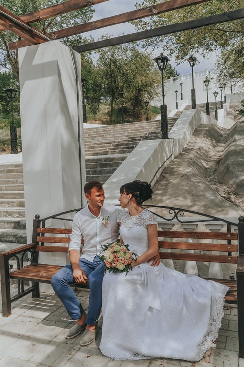Happy newlywed couple sitting on bench