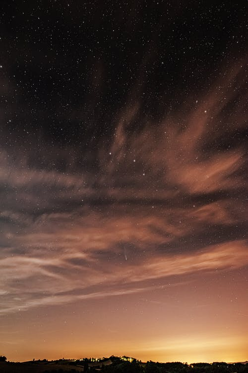 Long exposure spectacular scenery of colorful evening sky with glowing stars and floating light clouds over peaceful countryside