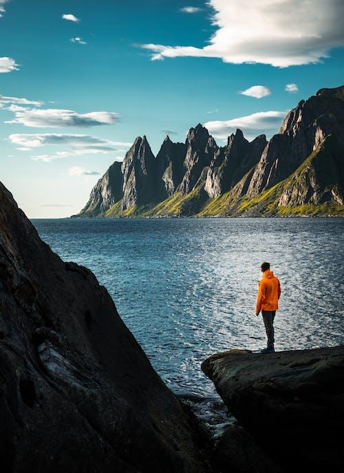 Man in Orange Shirt Standing on Rock Near Body of Water