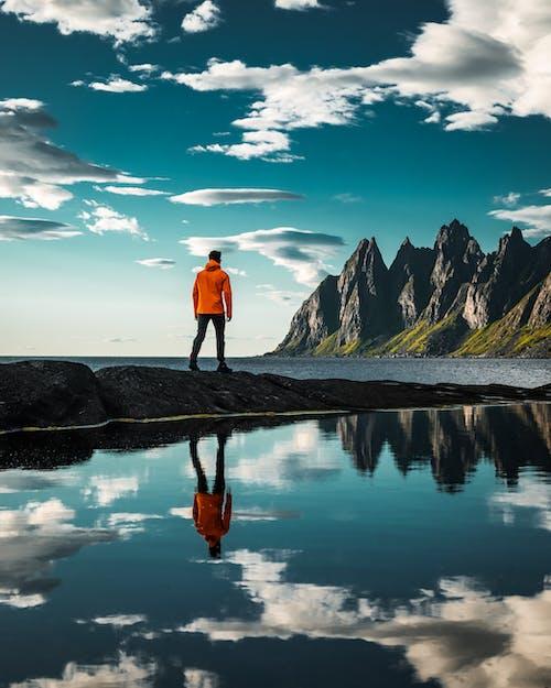Man in Red Jacket Standing on Rock Near Lake