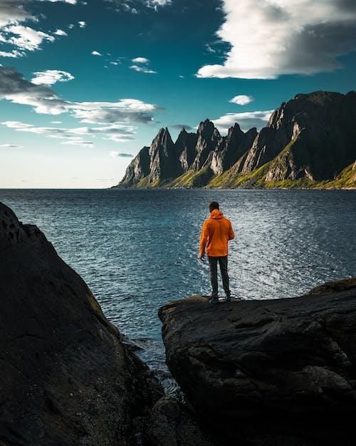 Man in Orange Jacket Standing on Rock Formation Near Body of Water