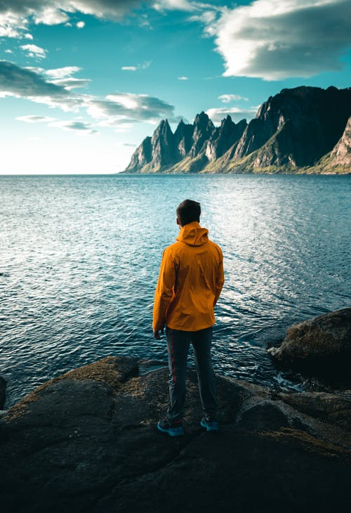 Man in Yellow Hoodie Standing on Rocky Shore