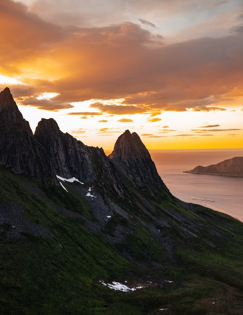 Montagne Verte Et Noire Au Bord De La Mer Pendant Le Coucher Du Soleil