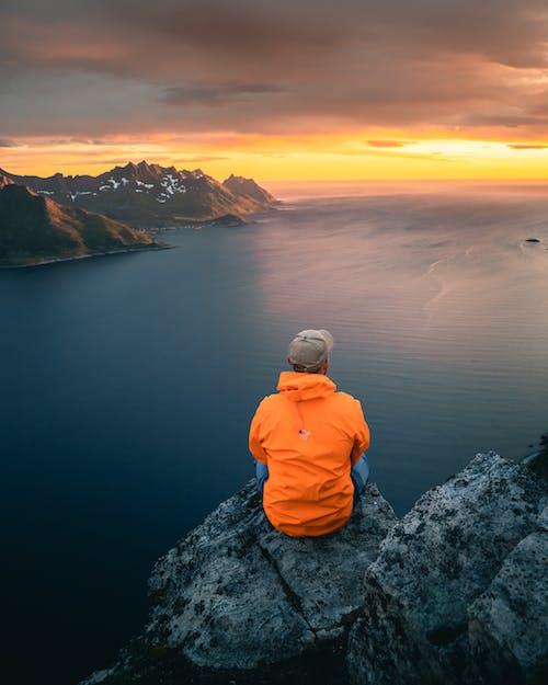 Person in Orange Hoodie Sitting on Rock Near Body of Water