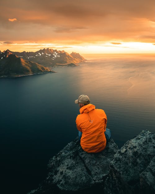 Person in Blue Jacket Sitting on Rock Formation Looking at the Sea