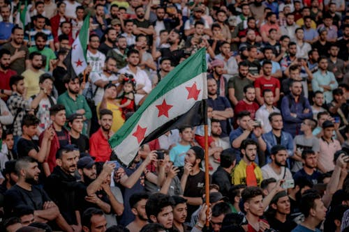 Faceless person demonstrating unofficial Syrian flag while standing in crowd