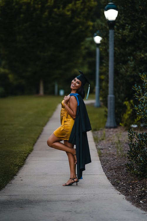 Full body of smiling female wearing elegant dress and graduation cap looking at camera while standing on narrow walkway with raised leg and cape on shoulder