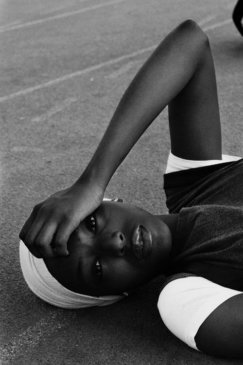 Black and white of charming African American woman in casual clothes lying with raised arm on ground on street and looking at camera in daytime