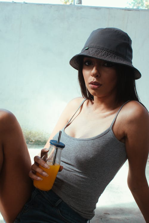 Woman in Gray Tank Top Holding Orange Plastic Cup
