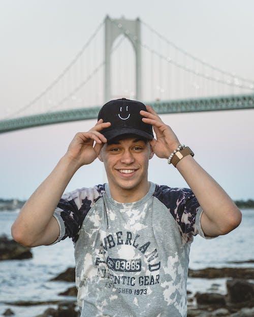 Man in Black and White Crew Neck T-shirt Wearing Black Cap Standing Near Bridge during