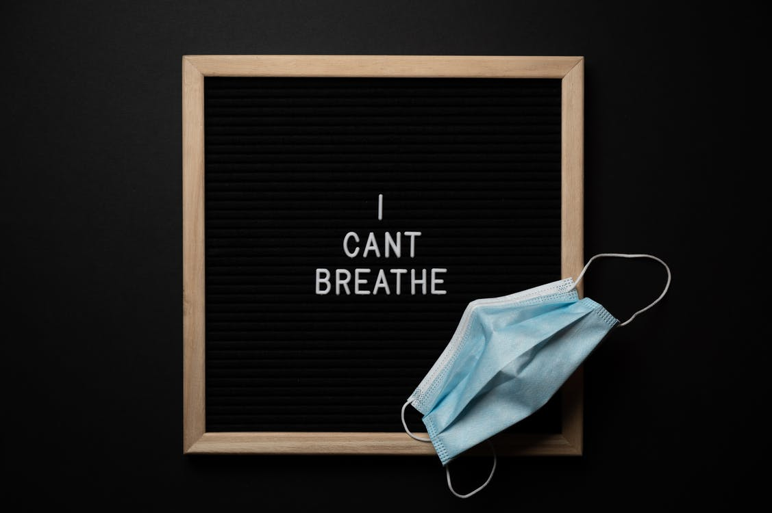 From above of face mask on blackboard with I Cant Breathe title during COVID 19 pandemic
