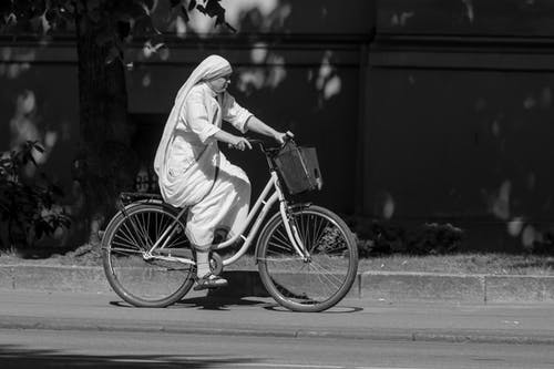 Black and white side view of female wearing traditional dress and headscarf riding bicycle on pavement on sunny day