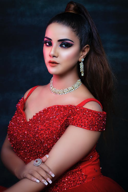 Elegant ethnic woman in red dress and accessories