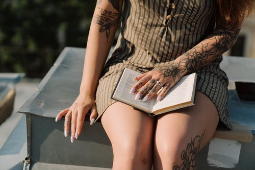 Woman in Brown and Black Stripe Dress Reading Book