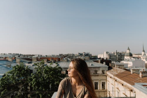 Woman in White and Black Striped Long Sleeve Shirt Standing on Top of Building